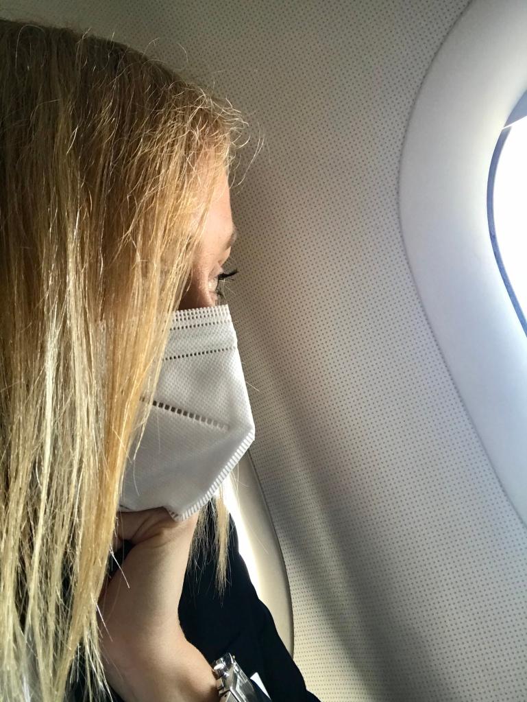 Pasajero de avión con mascarilla mirando por la ventana